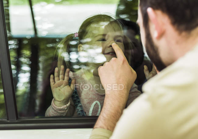 Father touching nose of girl behind car window — Stock Photo