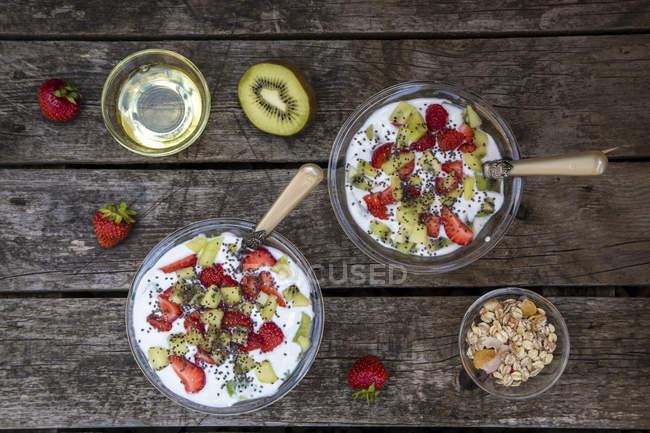 Миски йогурт полуниця ківі з круп, насіння чіа, агави сиропу на темного дерева — стокове фото