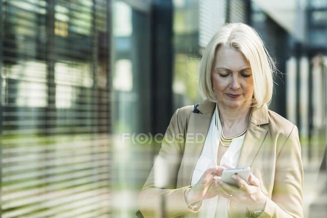 Donna matura che utilizza il telefono cellulare — Foto stock