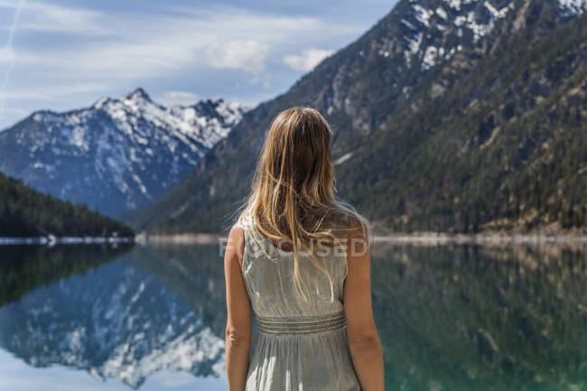 Austria, Tyrol, Lake Plansee, woman at lakeshore — Stock Photo