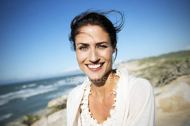Portrait of smiling woman with blowing hair on the beach — Stock Photo