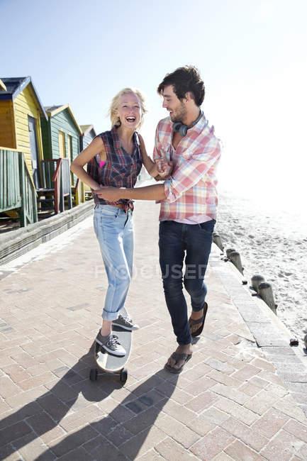 Jeune homme aidant amie sur planche à roulettes sur la promenade de la plage — Photo de stock