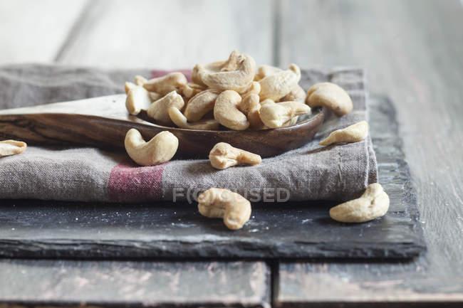 Закри дерев'яною ложкою горіхами кеш'ю, розміщені на рушник блюдо дерев'яний стіл — стокове фото