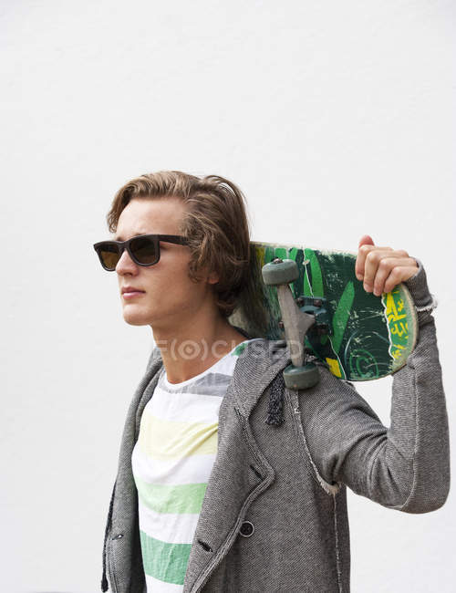 Portrait of young man wearing sunglasses holding skateboard on his shoulders — Stock Photo