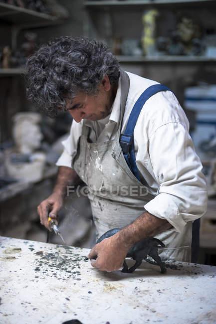 Art foundry worker finishing figurine — Stock Photo