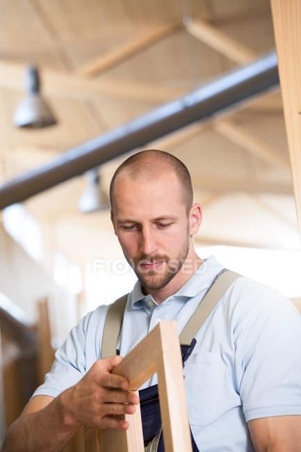 Carpenter examining piece of wood — Stock Photo