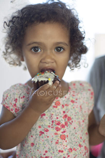 Mixed race girl eating cup cake — Stock Photo
