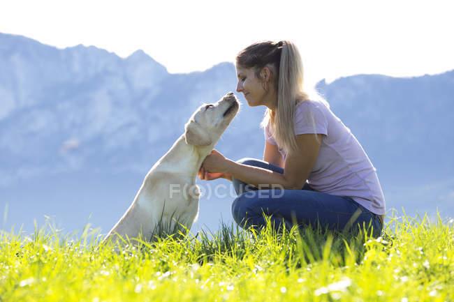 Donna con Labrador Retriever sul prato alpino — Foto stock