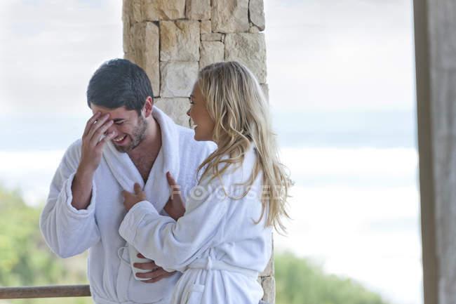 Счастливая молодая пара в халатах в пляжном домике — стоковое фото