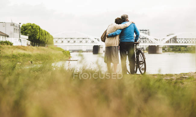 Back view of senior couple standing arm in arm at water's edge — Stock Photo