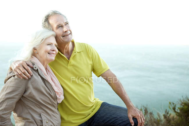 Portrait of happy senior couple in front of the sea — Stock Photo