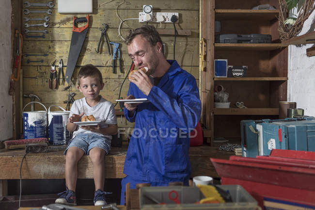 Father and son working in home garage having lunch break — Stock Photo