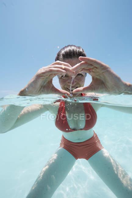 Malediven, Frau Gestaltung ein Herz mit den Händen im seichten Wasser — Stockfoto