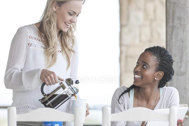 Dois amigos com cafetiere e tablet digital — Fotografia de Stock