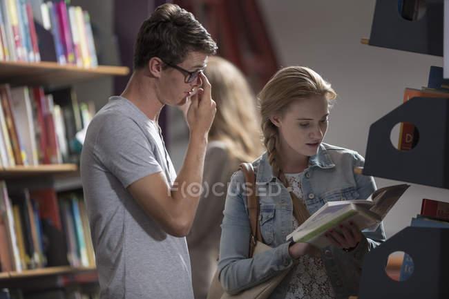 Студенты с книгой в библиотеке — стоковое фото