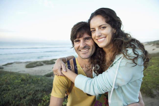 Happy couple embracing at the coast — Stock Photo