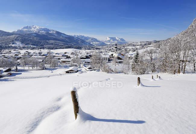 Germania, Baviera, Alta Baviera, Chiemgau, Veduta di Reit im Winkl in inverno, Unterberghorn e Kaiser montagne sullo sfondo — Foto stock