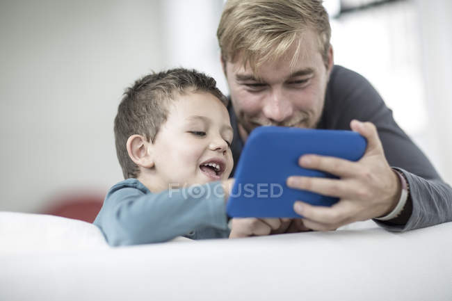 Father and little son on couch using tablet — Stock Photo