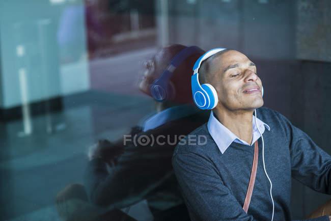 Человек в наушниках, прислонившийся к стеклу — стоковое фото