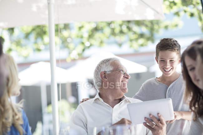 Abuelo y nieto con digital portátil en el restaurante - foto de stock
