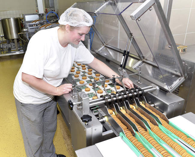 Woman controlling cookies on production line in a baking factory — Stock Photo