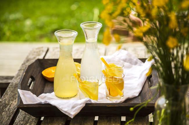 Tablet con caraffe e bicchieri di limonata fatta in casa e aranciata — Foto stock