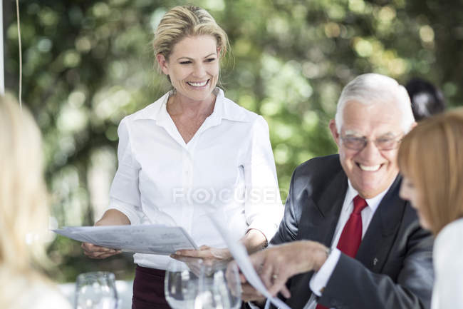 Cameriera di spiegare il menu ai clienti al tavolo — Foto stock