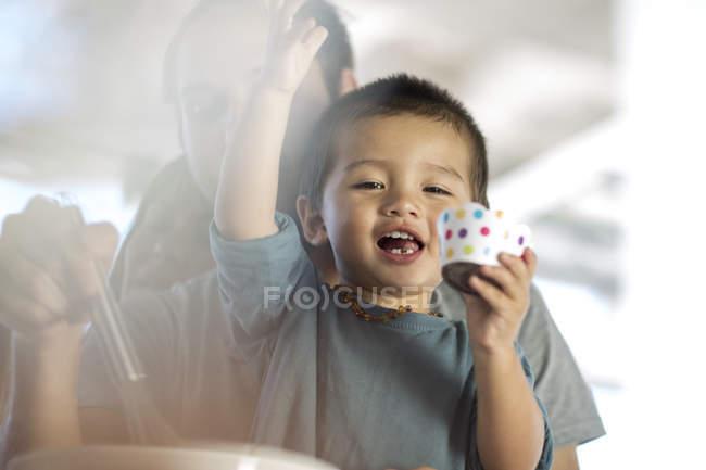 Маленький хлопчик щасливо тримає Кубок торт, сім'ї у фоновому режимі — стокове фото