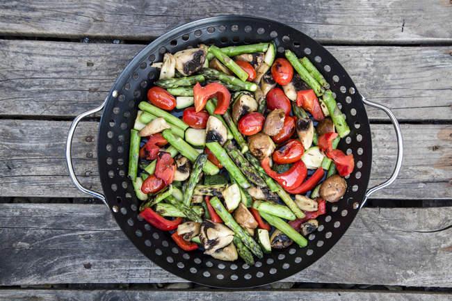 Legumes grelhados em uma cesta de grelha em madeira — Fotografia de Stock