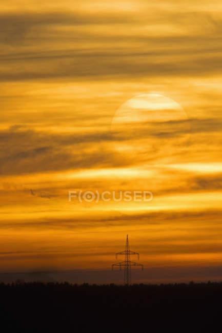 Allemagne, Bavière, pylônes électriques et soleil du soir — Photo de stock