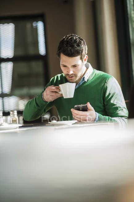 Menschen trinken Kaffee und mit Handy — Stockfoto