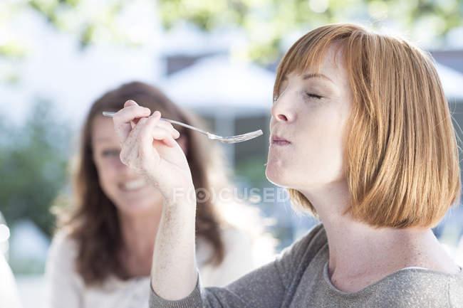 Jovem mulher comendo bolo copo — Fotografia de Stock