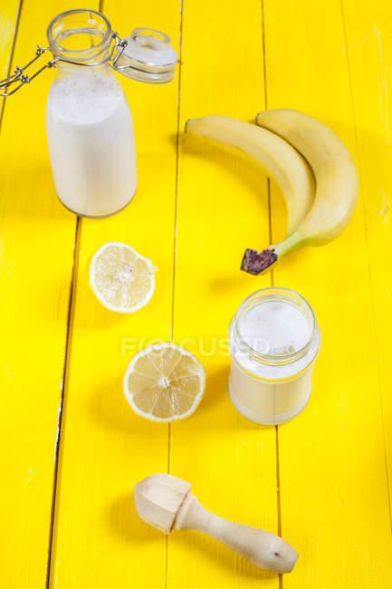 Smoothie banane citron sur fond jaune — Photo de stock