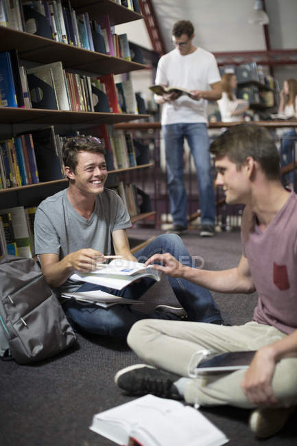 Two students communicating in a library — Stock Photo