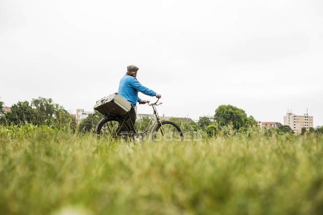 Senior man transporting suitcase on his bicycle — Stock Photo