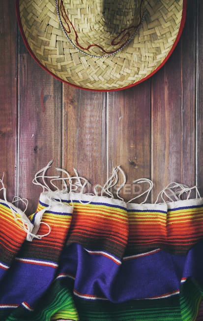 Top view of traditional Mexican serape and sombrero on wooden background — Stock Photo
