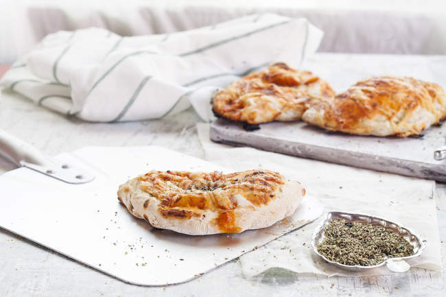 Pizzas Calzone on white wooden board with seasoning — Stock Photo