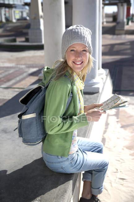 Turista che si siede sul lungomare con mappa — Foto stock