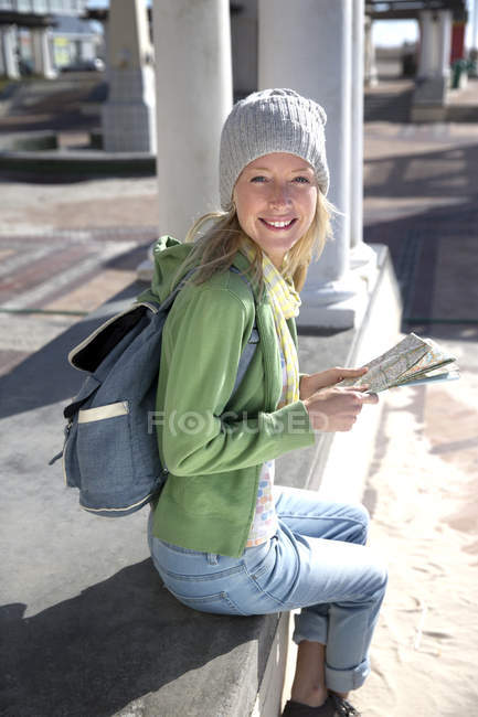 Tourist sitting on promenade with map — Stock Photo