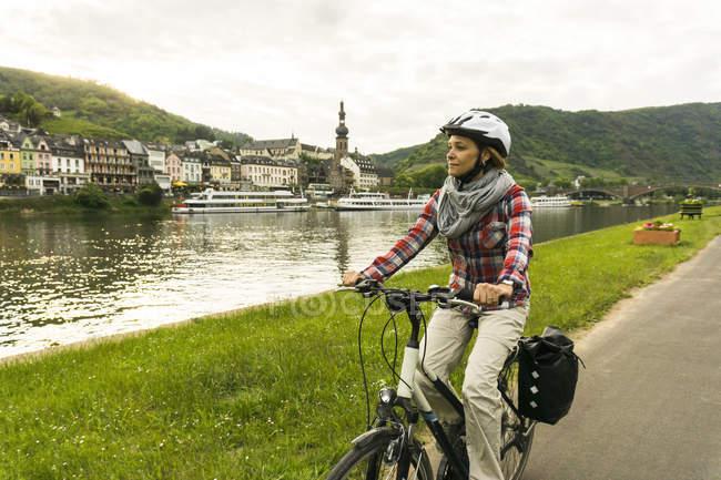 Alemania, Cochem, mujer montar a bicicleta a lo largo de la Ribera del Mosela - foto de stock