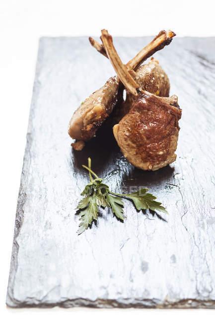Nahaufnahme von drei Lammkoteletts und Petersilie Blätter auf Schiefer — Stockfoto