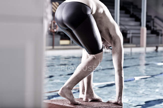 Swimmer in indoor pool in starting position — Stock Photo
