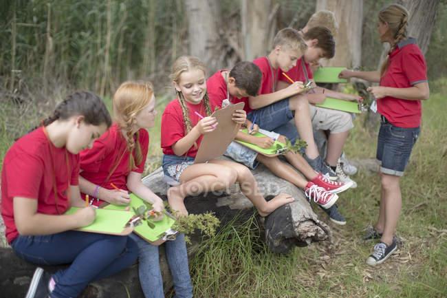 Bambini e donna con gli Appunti di esplorare la natura all'aperto — Foto stock