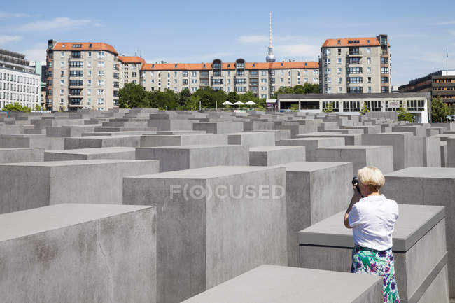 Germania, Berlino, Memoriale dell'Olocausto, Donna matura che fotografa stele — Foto stock