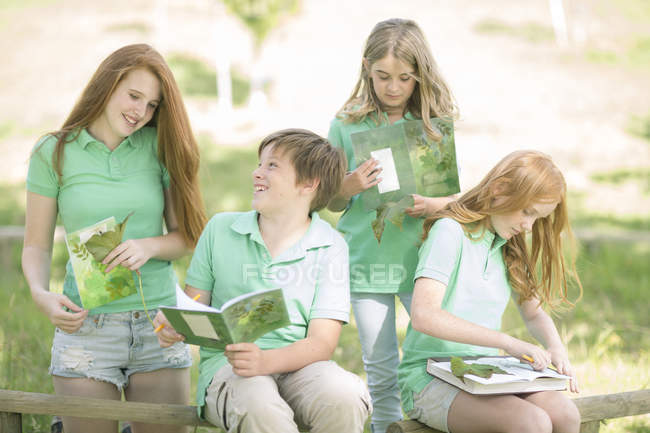 Group of pupils with exercise books and leaves in a park — Stock Photo