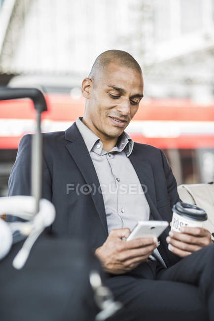 Businessman at the train station looking on smartphone — Stock Photo