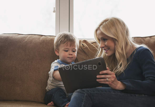 Мать и маленький сын сидят на диване, используя цифровой планшет вместе — стоковое фото