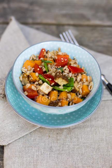 Veganer Salat mit Dinkelweizen, Sesam, Tofu, roter Paprika, Schneeerbsen und Karotten in Tonschüssel serviert — Stockfoto