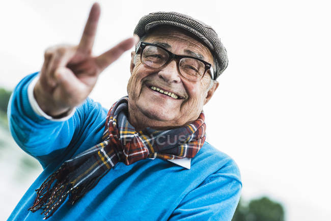Portrait of happy senior man showing victory sign — Stock Photo
