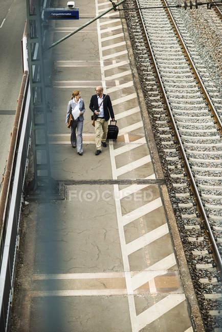 Businessman and businesswoman walking on railway platform — Stock Photo